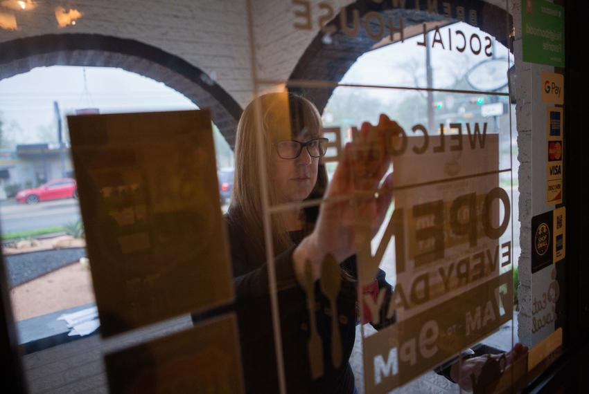 Brentwood Social House owner Suzanne Daniels tapes store hours and instructions on how to order on the store's front door. T…