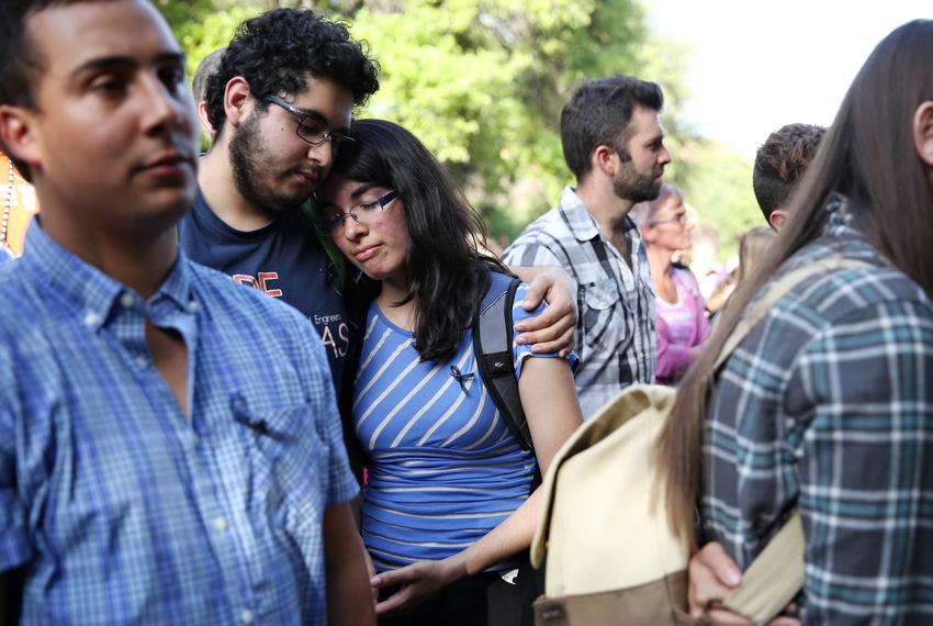 UT students Alfonso Galindo holds onto Erica Gomez during a community gathering in honor of Haruka Weiser on the Universit...