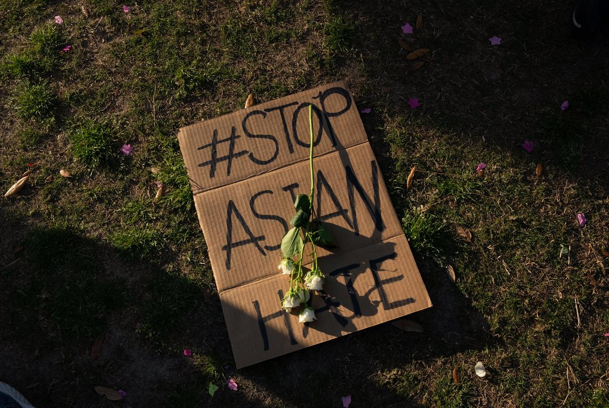 Flowers lay atop a sign at Discovery Green on March 20, 2021, in Houston. People gathered for the Stop Asian Hate Vigil and Rally after a man killed eight, including six Asians, in a mass shooting at three Atlanta spas.