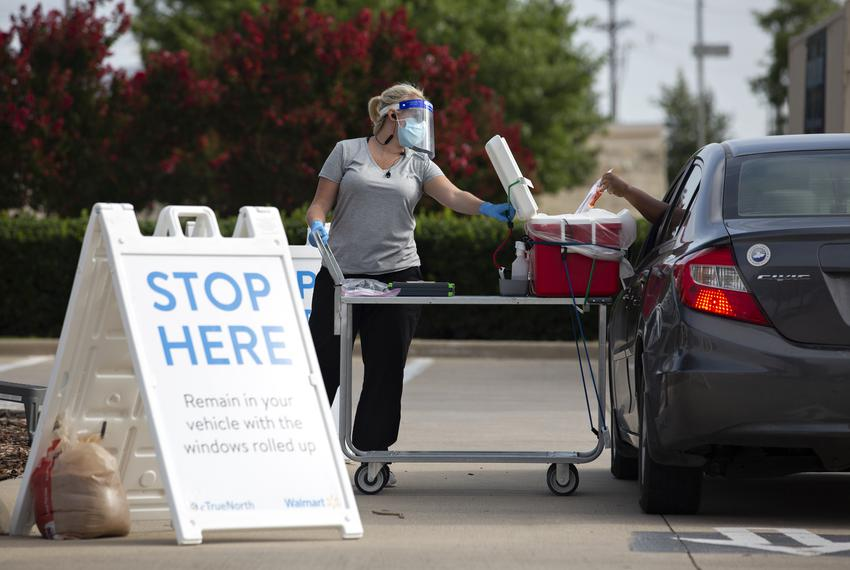 Pharmacist Emily Smith opens a cooler for a patient to place their self-swab coronavirus test at a Walmart drive-thru test...