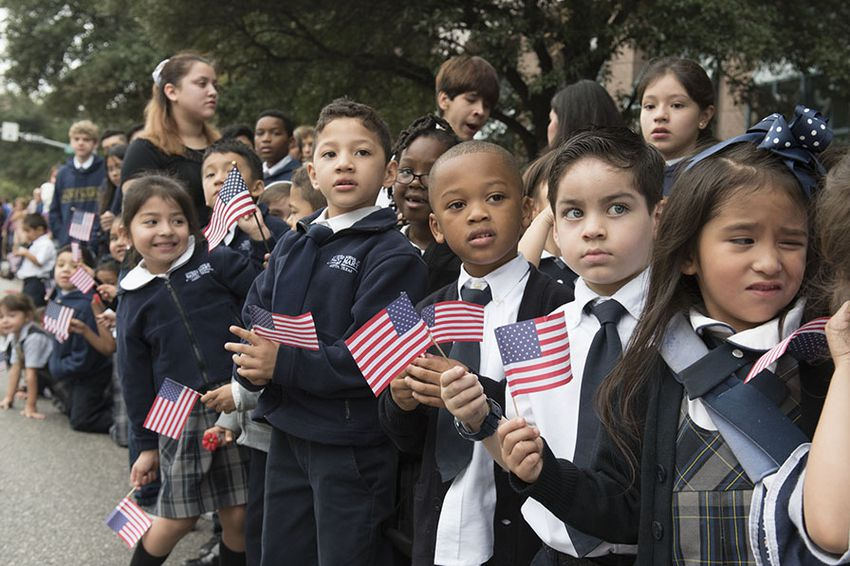 Schoolchildren watch the Veterans Day parade on Congress Avenue on Nov. 11, 2015.