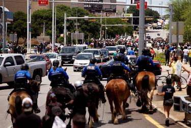 Police officers on horseback approach a crowd gathered to protest the deaths of George Floyd and Mike Ramos, in Austin on May 30, 2020.