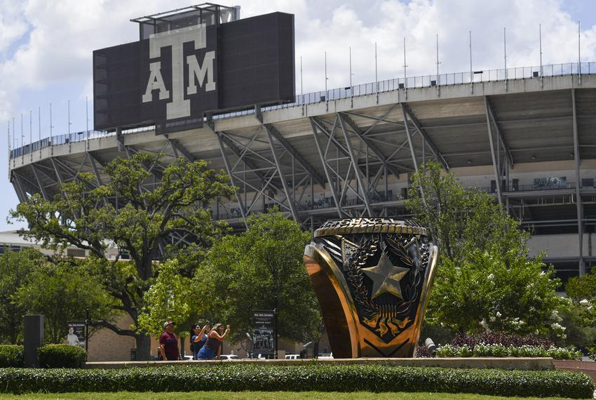 People take photos with the 3-ton bronze replica of the Haynes Aggie Ring at Texas A&M University on Monday, June 15, 2020 i…