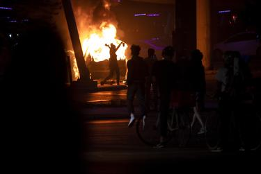 A protester walks in front of a burning car while a group of people observe. Protesters set the car on fire underneath Interstate 35, near Seventh Street in downtown Austin. May 30, 2020.