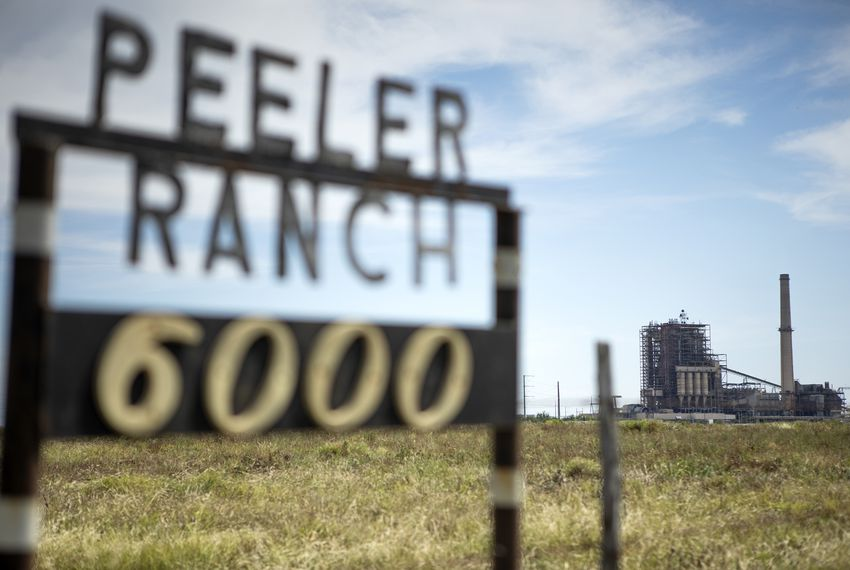 The San Miguel Electric Cooperative power plant can be seen in the background of a sign for the Peeler Ranch on April 26, 2019.