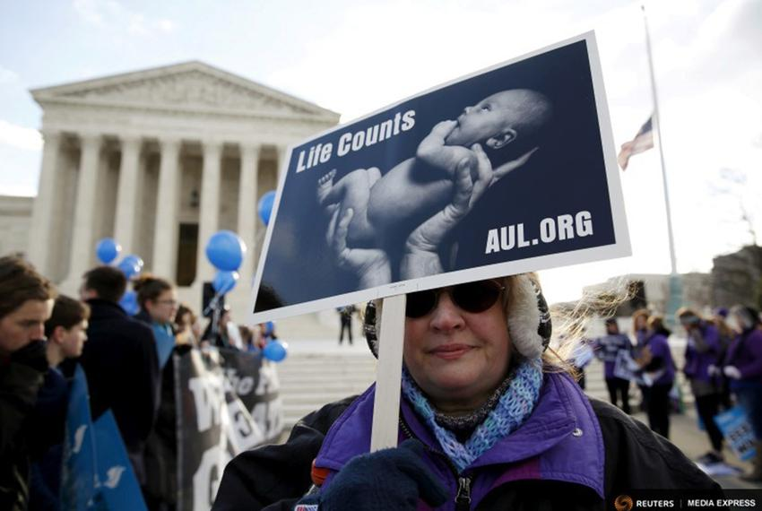 A protester holds up a sign in front of the U.S. Supreme Court on the morning the court takes up a major abortion case foc...