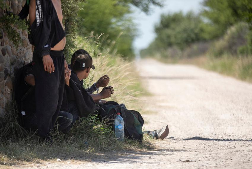 A group of migrants wait near a private road after being apprehended by Department of Public Safety officers at a train depo…
