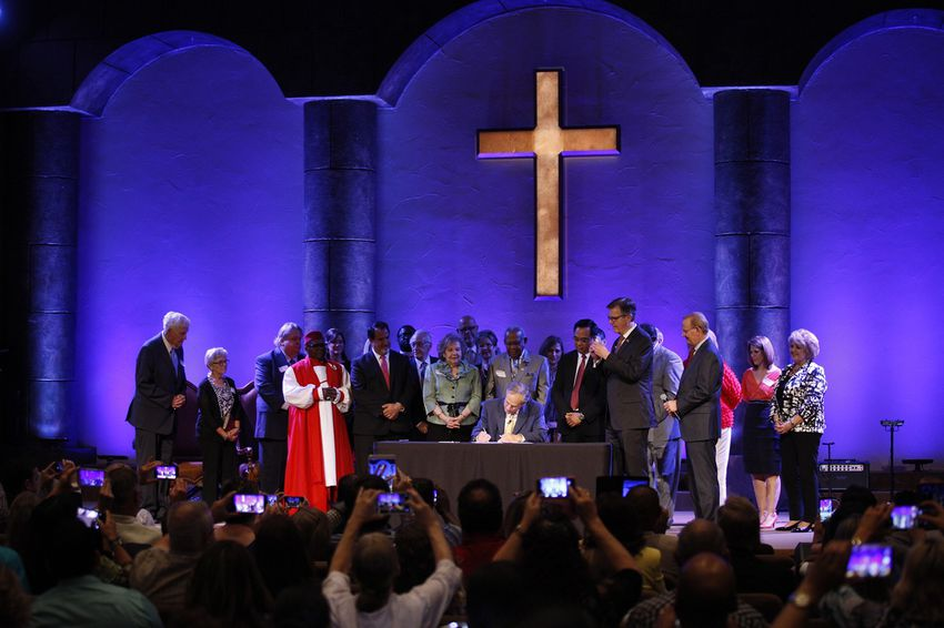 Gov. Greg Abbott ceremonially signsSenate Bill 24 into law as Lt. Gov. Dan Patrick and others look on atGrace Church in The Woodlands on May 21, 2017. The legislationshields pastors' sermons from government subpoena power.
