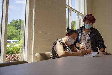 Onelia Orellana is assisted by Texas Department of State Health Services Specialist and Translator Maria Palacio as she fills out the forms needed to receive a COVID-19 vaccine at the Tennison Memorial United Methodist Church in Mt. Pleasant on May 7, 2021.
