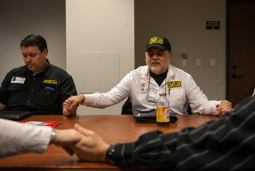 Michael Tummillo (right), the official volunteer chaplain at the Texas Department of Agriculture,  joins hands in prayer w...