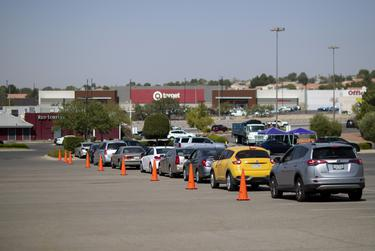 Cars line up on the first day of early voting in El Paso at the Sunland Park Mall drive-thru voting site on Oct. 13, 2020.