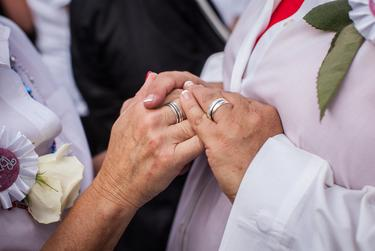 Pamela Holwerda and Kristin Taber hold hands after exchanging rings during a marriage ceremony that united over 40 same-sex couples in matrimony.