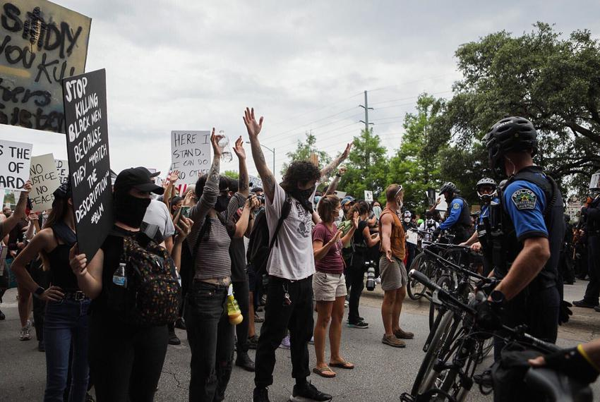 Arms raised, protesters face off with police in downtown Austin on May 31, 2020.