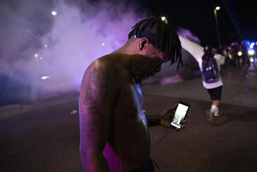 A protester covered in milk livestreams himself while Dallas Police tactical officers fire rounds of tear gas during a march in memory of  George Floyd on May 29, 2019.