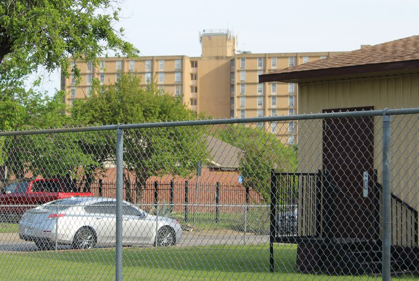 The Cliff Manor Apartments, a public housing building for elderly and disabled Dallas residents, looms behind a Stevens Park Elementary portable building in North Oak Cliff. More than half the people in the Dallas neighborhood live below the national poverty level.