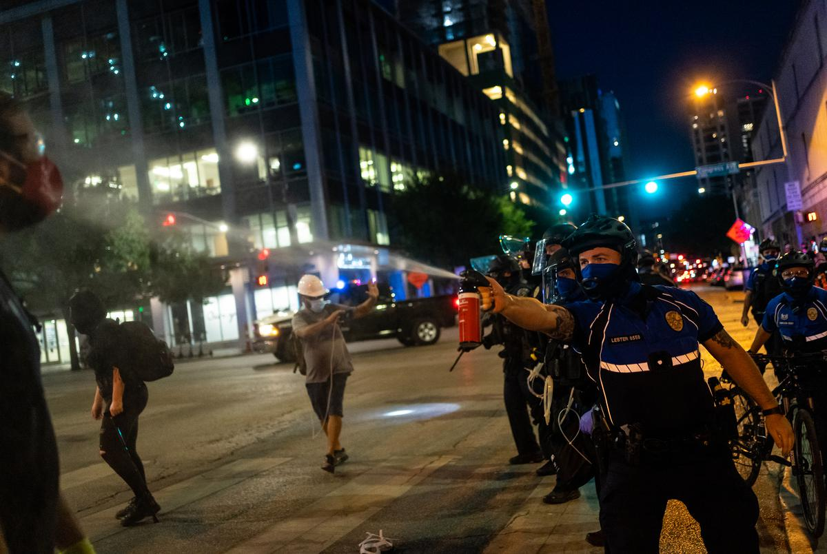 A police officer sprays a protester with pepper spray as demonstrators clash with police in riot gear in downtown Austin on August 1, 2020.