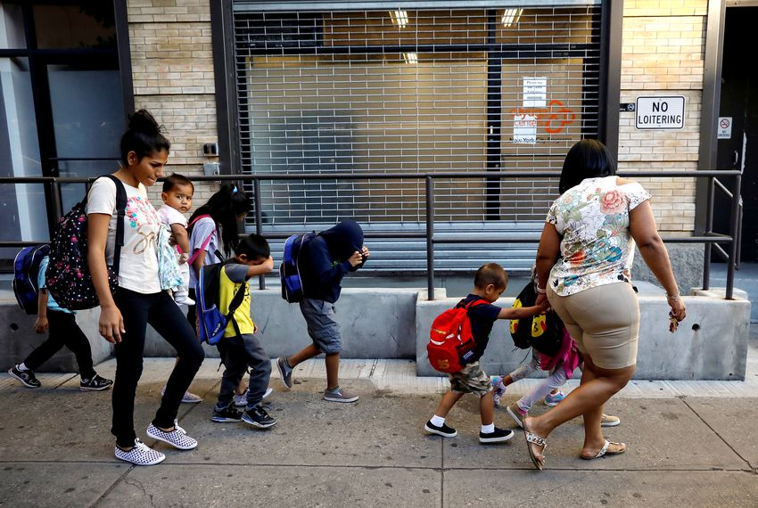 Children cover their faces as they are escorted to New York City's Cayuga Center, which provides foster care and other services to immigrant children separated from their families.