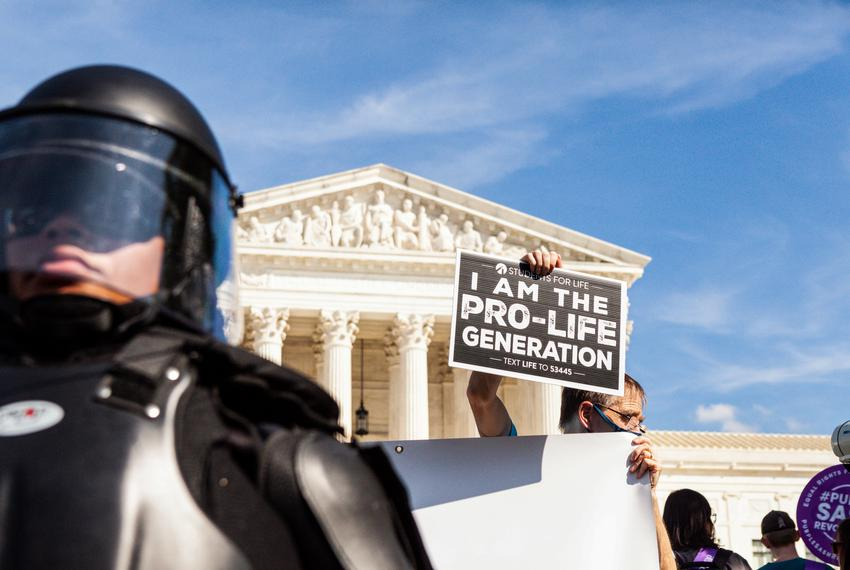 An anti-abortion counterprotester holds a sign behind a Capitol Police officer in riot gear as the Women's March for Abortio…