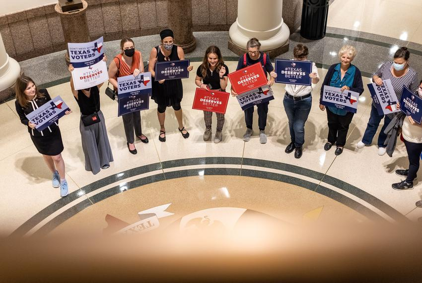 """Activists hold signs saying, """"Texas Deserves Better"""" outside a Senate committee hearing on proposed election reforms, at the…"""