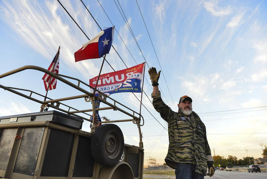 Kevin Rury waves to cars across from the polling station in Schertz early on Election Day morning.