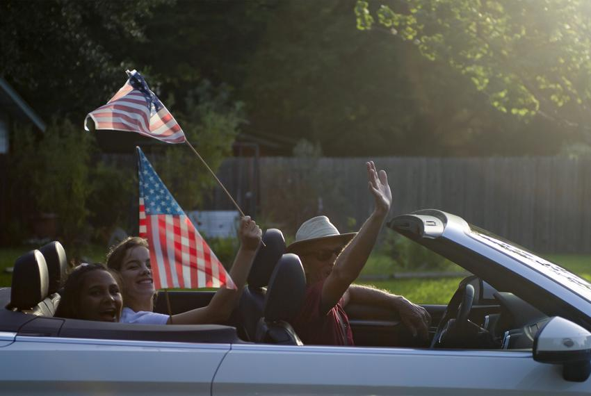 A family waves as they drive by a decorated house as part of Allandale Neighborhood's Reverse Parade for the Fourth of July …