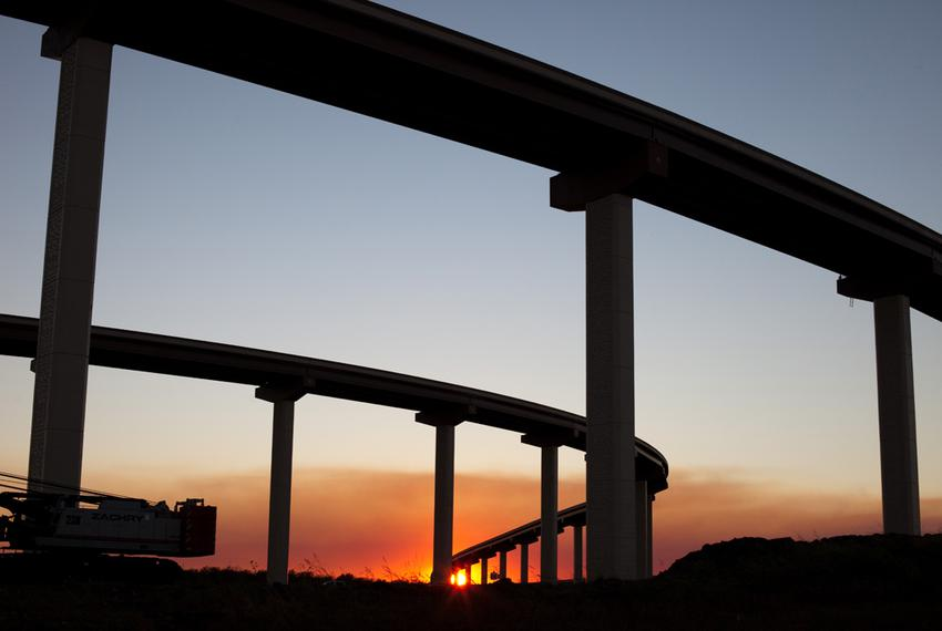 The sun sets through the smoke from the Bastrop wildfires near sunset at the intersection of highways 45 and 183 near Lockha…
