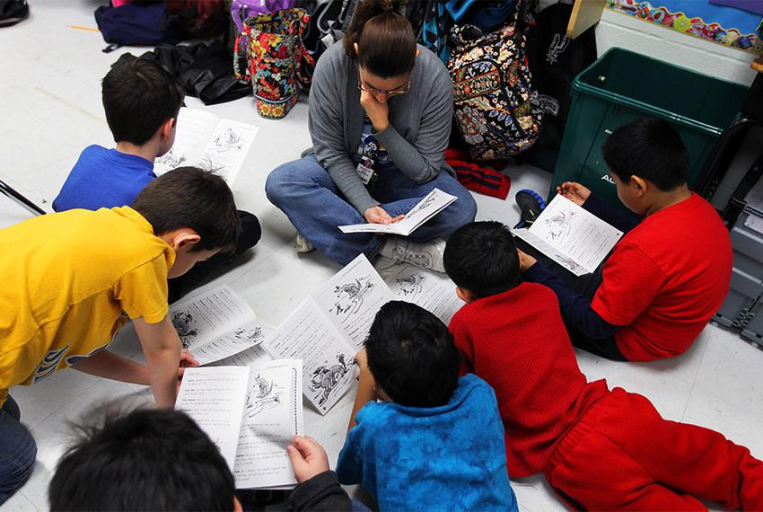 A reading assistant reads on the classroom floor with a small group of fourth graders at Wanke Elementary School in San An...