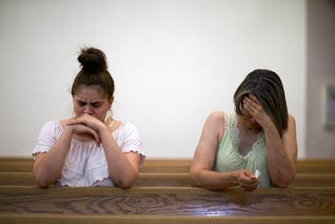 Nadra Alvarez, left, and her mother Angelina Alvarez pray after a candlelight vigil at a Catholic church, Saturday, August 3, 2019, in El Paso, Texas. Photo by Ivan Pierre Aguirre