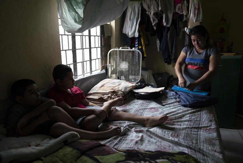 Marlen D. Cruz, 42, an asylum seeker from Honduras, looks for her immigration documents in a bedroom that a friend who is al…