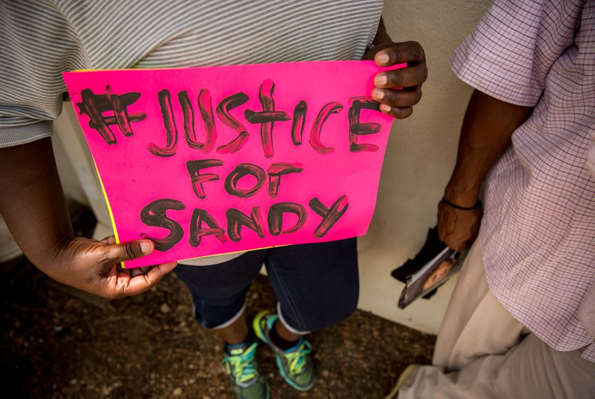 Hempstead resident Adrienne Holland holds a sign outside of the Waller County Jail where Sandra Bland, 28, was found dead.