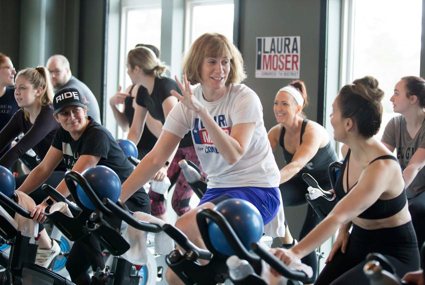 Laura Moser, center, talks with actress and activist Alyssa Milano, right, at a fundraising spin class in Houston on Saturda…
