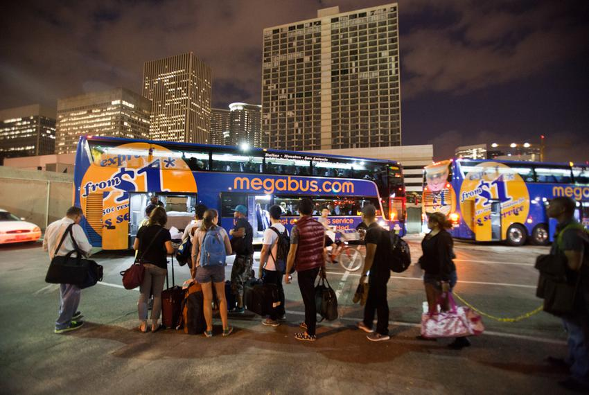 Passengers wait in line to board the Megabus to Austin at the Houston bus stop located at  815 Pierce St. on Sept. 27, 2013.