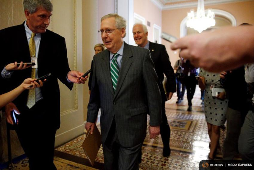 Senator Majority Leader Mitch McConnell and Senate Majority Whip John Cornyn are trailed by reporters as they walk to the...