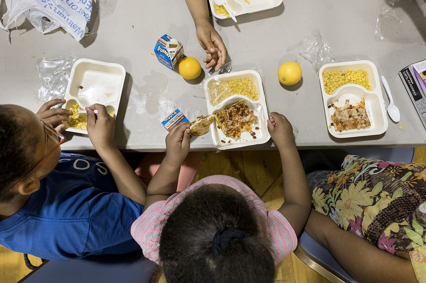 Siblings Stacy Hurd, 11, Angelica Hurd, 5, and Sheniya Hurd, 8, eat a free meal together at Jarvis Christian College in Hawkins, one of more than 70 sites the East Texas Food Bank sponsors in the summer.