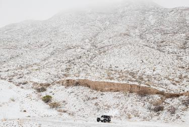 A Jeep drives offroad beneath the snow covered Franklin Mountains in El Paso, Texas on February 15, 2021.