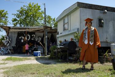 Viky Cruz poses for a portrait outside her family's trailer in Alvin. Viky Cruz, 18, whose house burned down during the school year, graduated from Alvin High School on Sat, June 6, 2020.