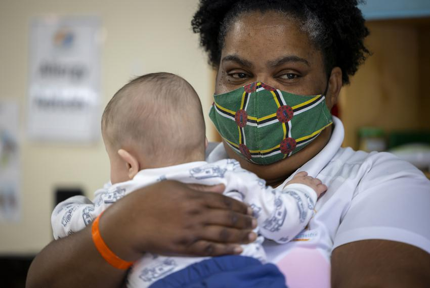 Museum District Childcare Center's Louvaine Reid comforts a baby on their first day at the center on Sept. 1, 2021. The cent…
