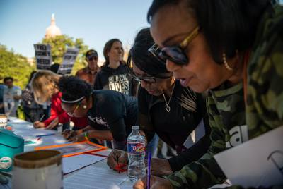Rodney Reed's cousins Delores Ferguson, center, and Patricia Reed, right sign a clemency letter before a rally in front of the Texas Governor's Mansion on Nov. 9, 2019, in Austin. Rodney Reed is scheduled for execution Nov. 20, 2019, in Huntsville, for the 1996 strangling of Stacey Stites in Bastrop County. His family and activists are fighting to prove his innocence.