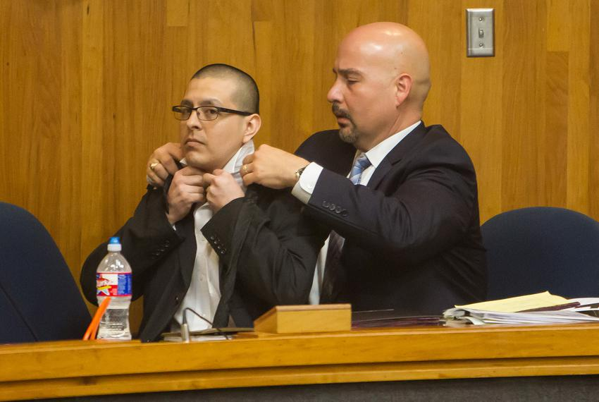 Lead defense attorney Carlos Garcia assists defendant Joel Luna in putting on a tie prior to Luna's murder trial in Brownsvi…