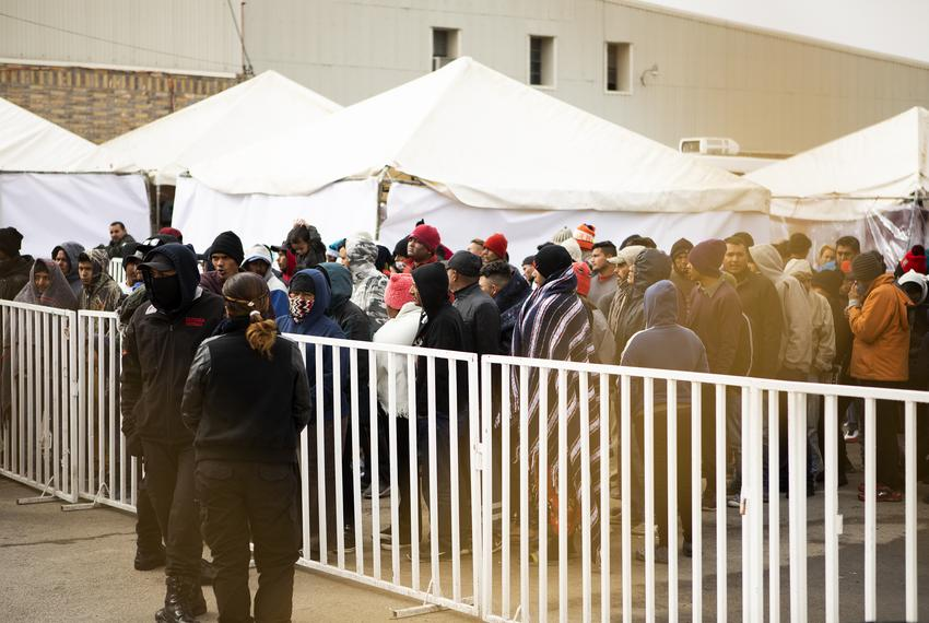 Migrants wait in line to purchase food items from a trailer located outside of the shelter where they're currently being hel…