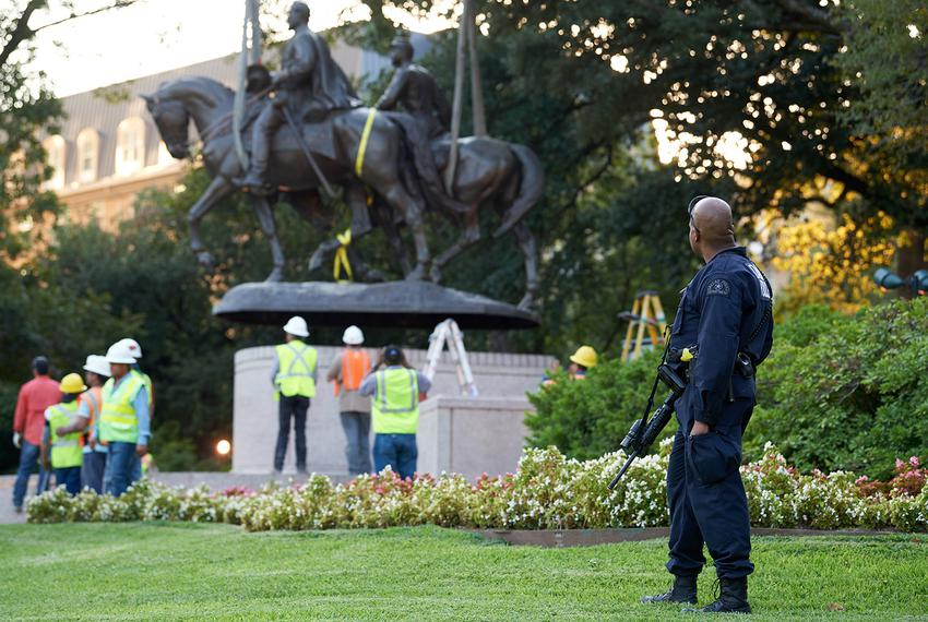 An Dallas police officer looks on as a crane lifts a statue of Robert E. Lee from Lee Park in Dallas on Thursday, Sept. 14, …