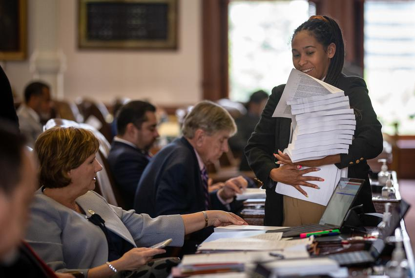 A staffer passes out papers during session on the House floor at the state capitol on May 25, 2021.