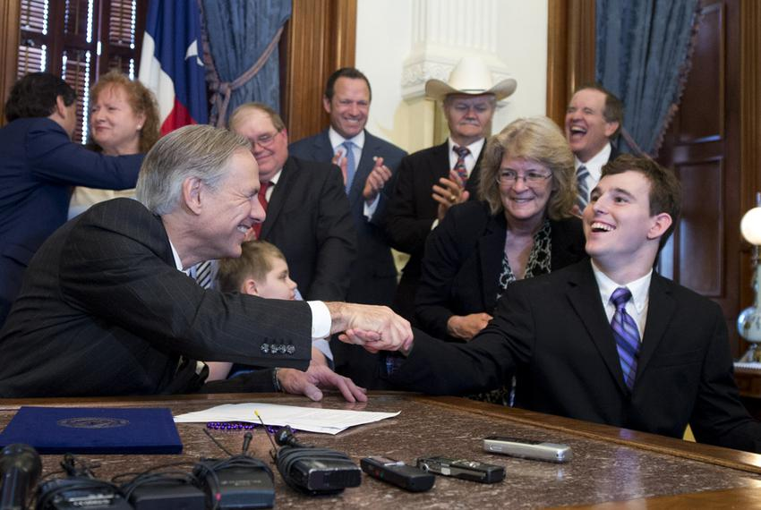 Gov. Greg Abbott, l, shakes hands with student Zachariah Moccia, 25, of San Antonio after signing SB 339, allowing limited...