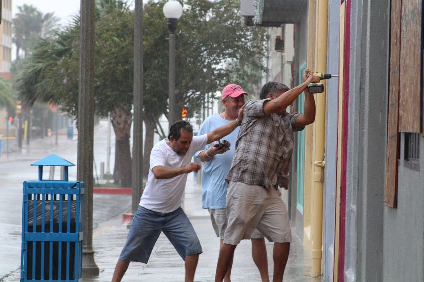 Ramiro Jimenez (left), Kevin Murphy (in baseball cap) and Gary Acuna (with drill) board up Tease Salon, which Murphy owns, ahead of Hurricane Harvey on Friday morning, Aug. 25, 2017.