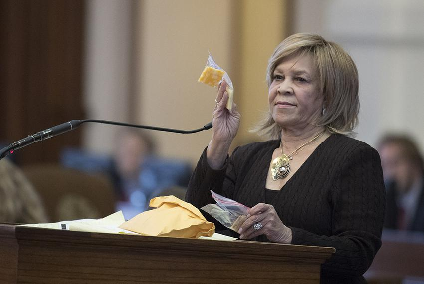 State Rep. Helen Giddings, D-Desoto, holds up a sample of a piece of cheese given to students who lack money to pay for scho…