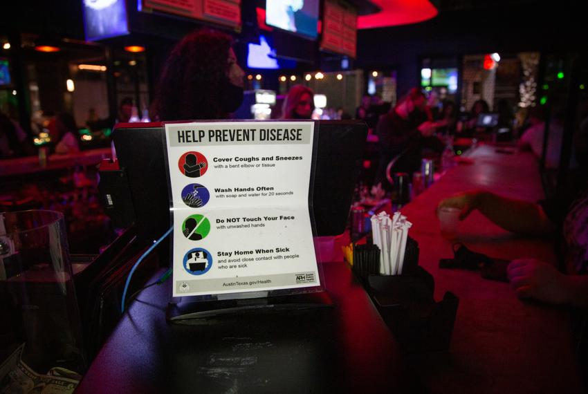 A sign asks customers to follow COVID safety precautions at the Green Light Social bar in Downtown Austin on March 12, 2021.