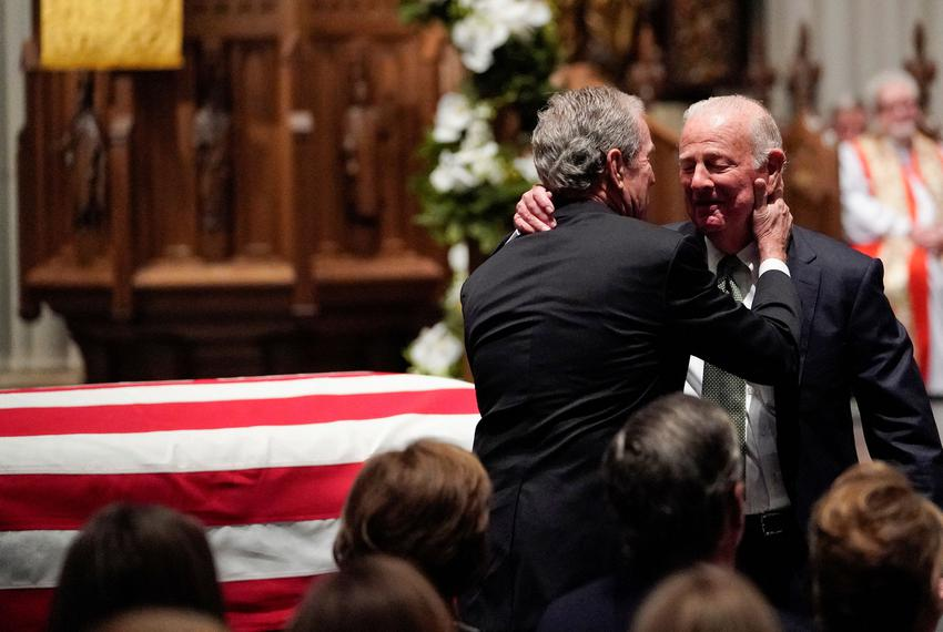 Former President George W. Bush embraces former Secretary of State James Baker after he gave a eulogy during the funeral f...