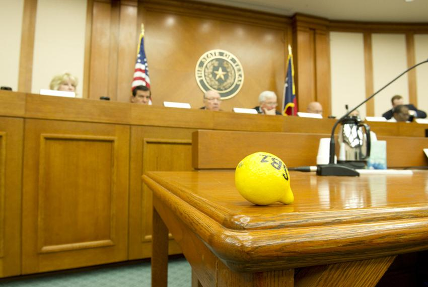 A lemon is left on the desk by a protester as the Senate Finance Committee voted to use the rainy day fund to balance the st…