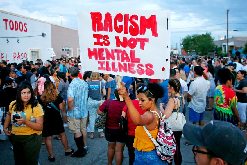 A woman holds a sign after a silent march to Las Americas Immigrant Advocacy Center for the victims of the Walmart shootings…