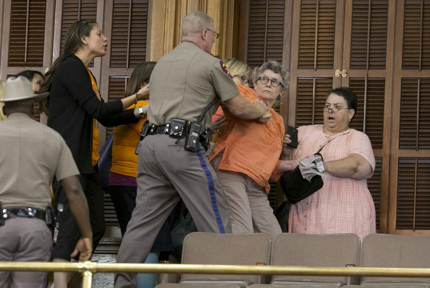 A woman in the Senate gallery pushes back against a police officer and is later arrested during the last hour of the Senate …